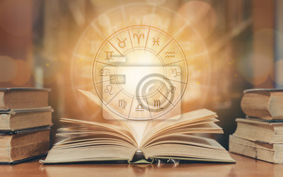 Naklejka Zodiac sign horoscope astrology and constellation study for foretell and fortune telling education course concept with horoscopic wheel over old book in school library