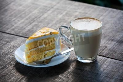 Naklejka Żółte ciasto z filiżanki latte kawy na starym stole drewna