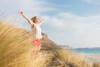 Naklejka Zrelaksowana kobieta, ręce wyrastające, cieszące się słońcem, swobodą i życiem, piękna plaża. Młoda dama czuje się wolna, zrelaksowana i szczęśliwa.