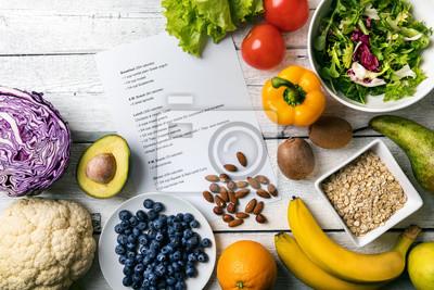 Naklejka zrównoważony plan diety ze świeżymi warzywami i owocami na stole