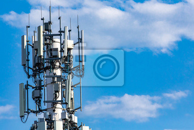 Obraz A closeup and detailed view of various GPS, cellphone, 3G, 4G and 5G equipped telecommunication tower as seen on cloudy blue sky with copy space