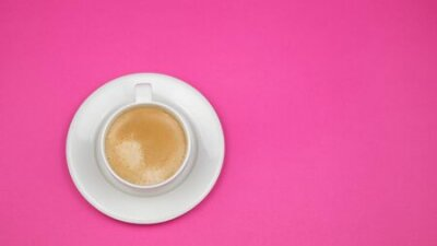 Obraz A cup of black coffee on pink background. View from above. copy space.
