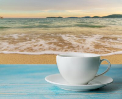 A cup of coffee with blurred beach sunset or sunrise and cloud sky in twilight