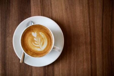 Obraz a cup of Latte art coffee on wood background with copy space