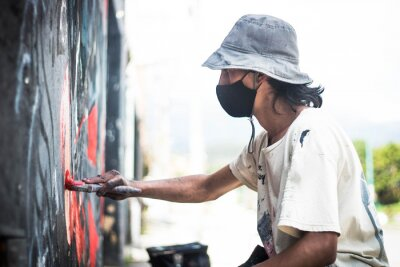 Obraz A handsome graffiti artist in a face mask bucket hat and paint-stained clothes painting with a paintbrush on a wall