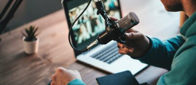 Obraz A man host streaming his audio podcast using microphone and laptop at his small broadcast studio, close-up