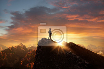 Obraz A man standing on top of a mountain as the sun sets. Goals and achievements concept photo composite.