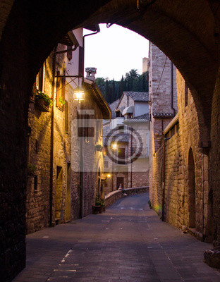 A medieval picturesque street in Assisi by night, view through arch