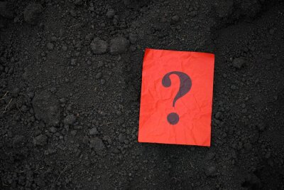 Obraz A red paper note with a question mark on it lying on soil