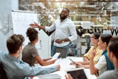 Obraz Achieving best results together. Young afro american businessman pointing at white blackboard and smiling while working with multicultural team in the creative office