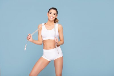 Obraz Active happy fit girl with centimeter.