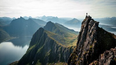 Obraz Adventurous man is standing on top of the mountain and enjoying the beautiful view during a vibrant sunset. Taken on top Senja, Norway