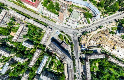 Obraz Aerial city view with crossroads and roads, houses, buildings, parks and parking lots. Sunny summer panoramic image