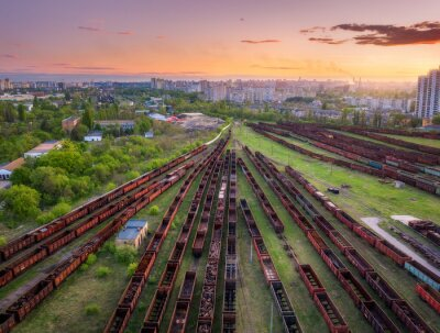 Aerial view of freight trains at sunset. Top view of railway station, wagons, railroad. Heavy industry. Industrial landscape with train in depot, buildings, city, orange sky at dusk. Transportation