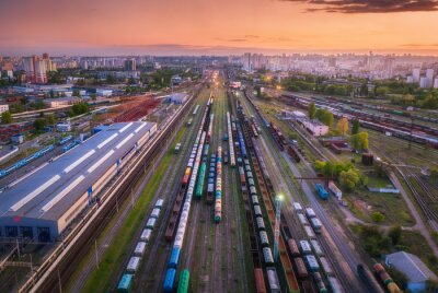 Aerial view of freight trains at sunset. Top view of railway station, wagons, railroad. Heavy industry. Landscape with train in depot, buildings, city, lights, colorful sky at night. Transportation
