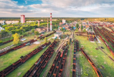 Aerial view of freight trains. Railway station with wagons. Heavy industry. Industrial landscape with train in depot, smoke stack, green trees, buildings, blue sky at sunset. Top view. Transportation