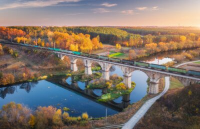 Aerial view of moving freight train on railroad bridge and river at sunset in autumn. Landscape with bridge, wagons, water, colorful trees, sky with gold sunlight in fall. Top view of railway station