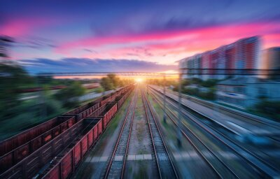 Aerial view of railroad and colorful sky with clouds at sunset with motion blur effect in summer. Industrial landscape with freight train, railway station, blurred background.  Railway platform