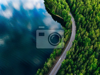 Obraz Aerial view of road between green forest and blue lake in Finland