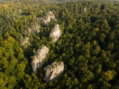 Obraz Aerial view to Dovbush Rocks in Bubnyshche at sunrise. Legendary ancient cave monastery in fantastic boulders amidst beautiful scenic forests in Carpathian Mountains, Ukraine