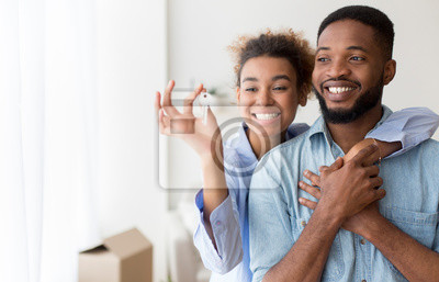 Obraz African American Couple Holding Key Embracing Standing In New Flat