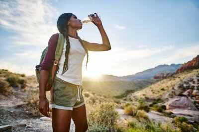 Obraz african american woman taking a break to drink from water bottle while hiking at red rock canyon nevada