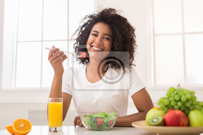 Obraz African-american woman with vegetable salad and fresh juice