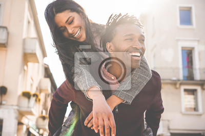 Obraz African couple having fun outdoor in city tour - Young people lovers enjoying time together during vacation journey - Love, fashion, travel and relationship concept - Focus on woman face