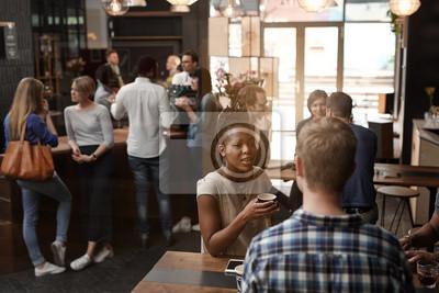 Obraz Afrykańska kobieta rozmawia z przyjacielem w środku ruchliwej kawiarni