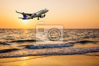 Airplane come down on the land with beach sunset or sunrise