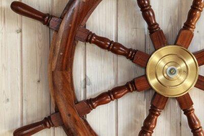 Obraz Altes Steuerrad eines Schiffes się Holzwand einer