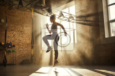 Obraz Always in good shape Full length of athletic woman in black sport clothing exercising in professional gym.