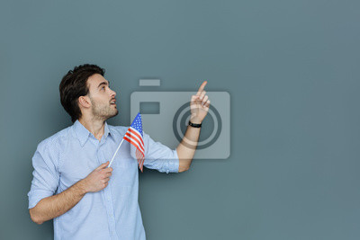 american-citizen-pleasant-nice-happy-man-holding-the-us-flag-and-looking-in-the-direction-of-his-hand-while-being-a-us-patriot-400-117032756.jpg