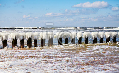 An icy wooden breakwater on a sunny day