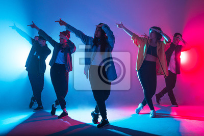 Obraz Animation group of young women and men dancing over red and blue dual color light on dark background