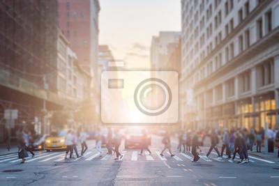 Anonimowy tłum ludzi przecina skrzyżowanie na ruchliwej ulicy Nowego Jorku na Manhattanie z tłem światła słonecznego