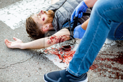 Obraz Applying first aid to the injured bleeding man, wearing tourniquet on the arm after the road accident on the pedestrian crossing