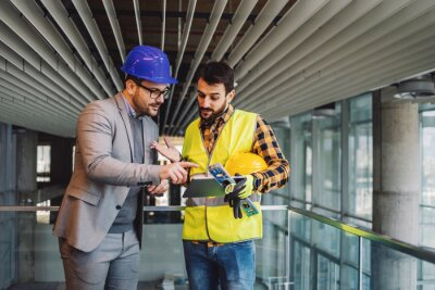 Obraz Architect and construction worker standing in building in construction process and looking at blueprints on tablet.
