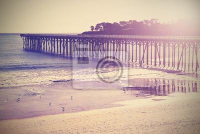 Archiwalne drewna most na plaży o zachodzie słońca, Kalifornia, USA.