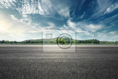 Obraz Asfaltowa droga i góra z niebem chmurniejemy krajobraz przy zmierzchem