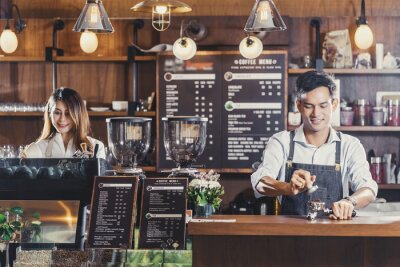 Obraz Asian Barista preparing cup of coffee, espresso with latte or cappuccino for customer order in coffee shop,bartender pouring milk,Small business owner and startup in coffee shop and restaurant concept