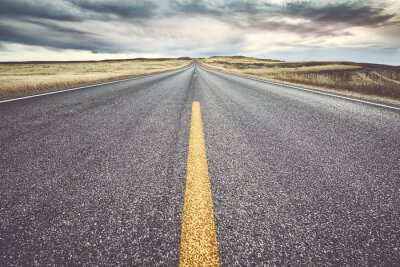 Asphalt road in Badlands National Park at sunset, focus on yellow lane, travel concept, color toning applied, USA.