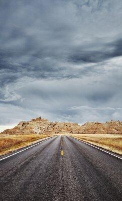 Asphalt road in Badlands National Park, focus on asphalt, travel concept, color toning applied, USA.
