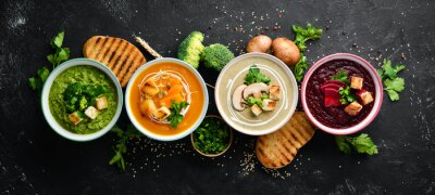 Obraz Assortment of colored vegetable cream soups. Dietary food. On a black stone background. Top view. Free copy space.