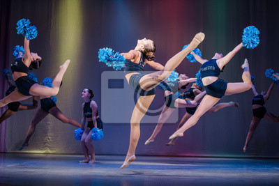 Obraz athletes perform on stage, young cheerleaders perform at the cheerleading championship, girls in a jump, girls are holding pompons, hands raised up, girls dancer practicing mixed dance and stretching