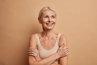 Obraz Attractive positive wrinkled fifty years old woman looks gladfully above keeps arms foded has well cared complexion healthy skin white teeth isolated over brown background. Beauty and age concept