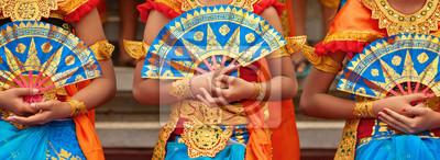 Obraz Azjatyckie tło podróży. Grupa piękne tancerki balinese kobiety w tradycyjnych strój Sarong z fanami w ręce tańczy Legong tańca. Sztuka, kultura indonezyjskich ludzi, festiwale wyspy Bali.