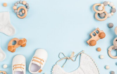 Obraz Baby shoes, bib and teether on pastel background. Organic newborn accessories
