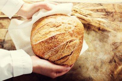 Obraz Baker gospodarstwa bochenek chleba na rustykalnym tle
