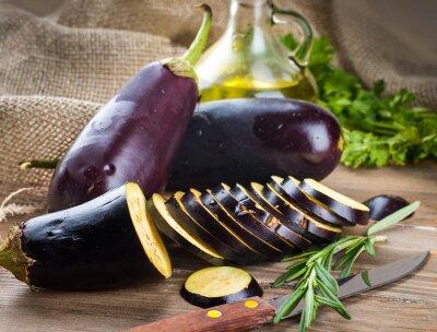 Obraz Bakłażan i oliwy z oliwek na drewnianym pokładzie